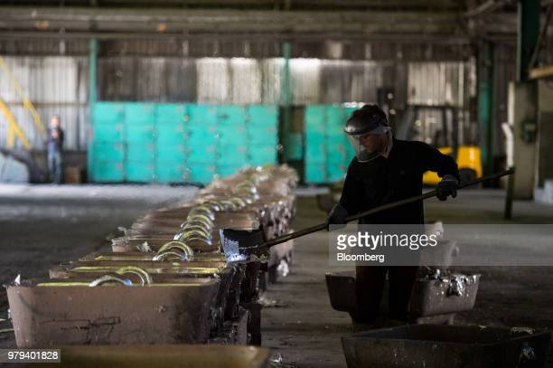 A worker scrapes surplus aluminium from an ingot mold at the Iran Aluminium Co plant in Arak Iran on Tuesday June 19 2018 As OPEC oil ministers meet...