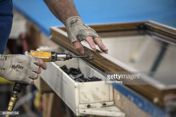 A worker screws a brace to a window frame at the Pella Corp manufacturing facility in Pella Iowa US on Thursday Feb 22 2018 The US Census Bureau is...
