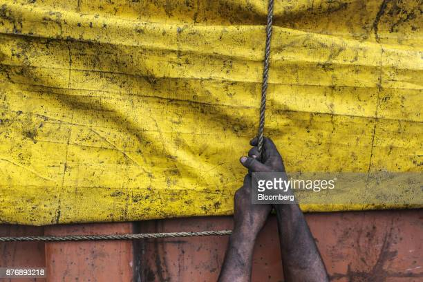 A worker secures a tarp on a truck laden with coal at Krishnapatnam Port in Krishnapatnam Andhra Pradesh India on Monday Aug 11 2017 Growth in gross...
