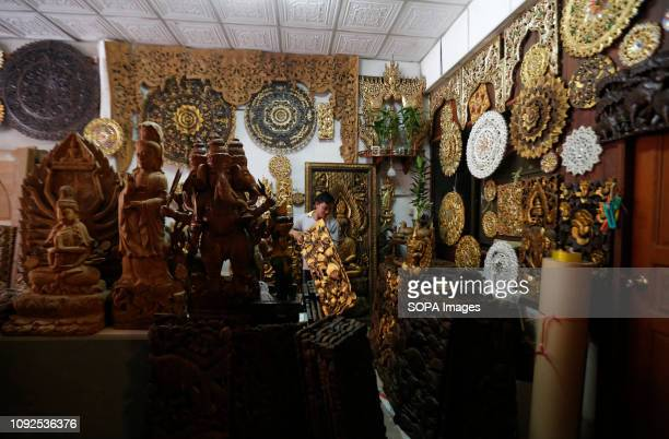 A worker seen arranging wooden souvenir in a store at a market in the Thai border town of Mae Sot