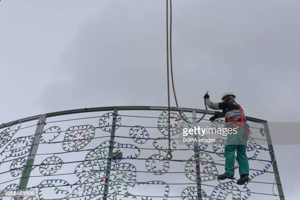 A worker seen preparing to install a giant Christmas tree at the Puerta del Sol square in Madrid ahead of Christmas celebrations