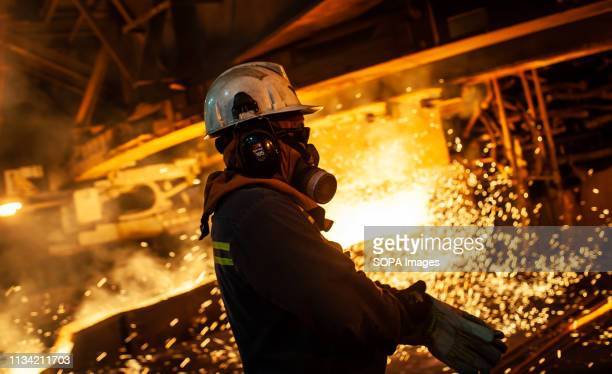 Worker seen with a gas mask supervising the flow of hot liquid metal as it flows from a furnace at the plant. Production of matte nickel at the PT...
