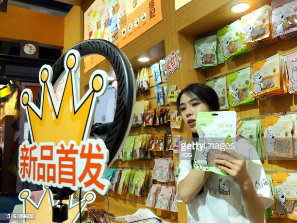 Worker sells pet food via live streaming during the 2021 Pet Fair Beijing at China National Convention Center on May 20, 2021 in Beijing, China.
