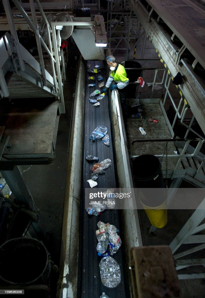 A worker separate different types of waste for recycling at a waste treatment plant in Palma de Mallorca on January 17, 2013. AFP PHOTO / Jaime REINA