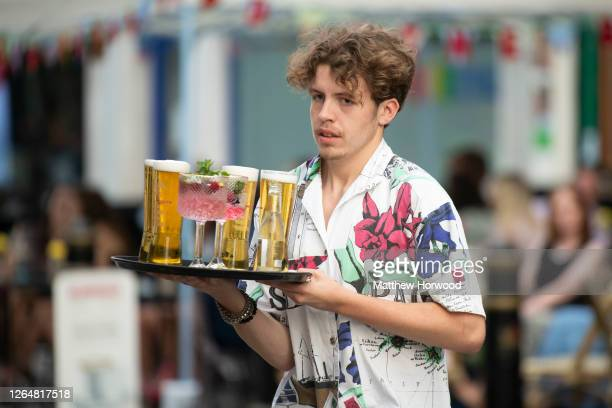A worker serves drinks at the Gin and Juice bar gin bar on August 08 2020 in Cardiff Wales Coronavirus lockdown measures continue to be eased as the...