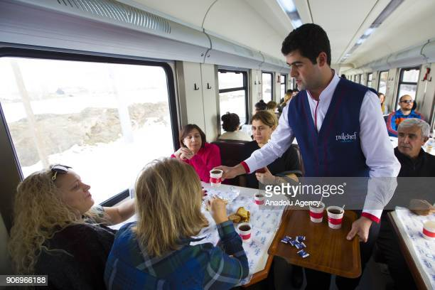 A worker serves tea to travelers on the Eastern Express which travels from Ankara to Kars in Kars Turkey on January 13 2018 With the starting of...