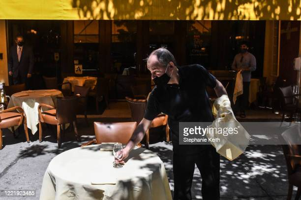 Worker sets an outdoor table for the Cipriani restaurant on June 22, 2020 in the SoHo neighborhood in New York City. New York City enters phase 2...