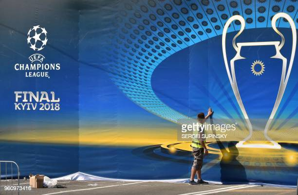 TOPSHOT A worker sets decoration in the fan zone of the 2018 UEFA Champions League Final in Kiev on May 21 ahead of the football match between Real...