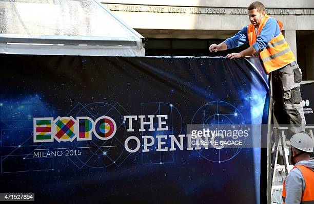 A worker sets up a banner at the opening venue of the Universal Exposition Milano 2015 EXPO2015 on April 29 in downtown Milan The Expo will run from...