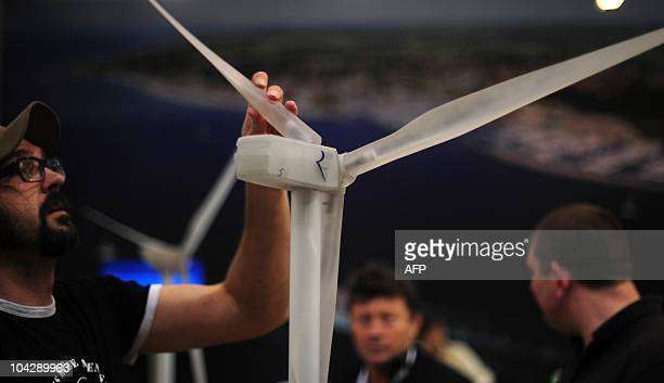 A worker sets up a model of a wind turbine at the Wind Energy 2010 fair on September 20 2010 in Husum northern Germany The fair for Wind Energy trade...