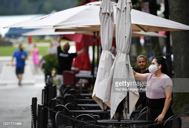 Worker sets up for restaurant diners along King Street on Thursday July 23, 2020 in Alexandria, VA. The United States recently reached four million...