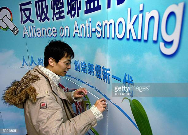 A worker sets up stage with a mural during a ceremony organized by the Alliance of AntiSmoking at the Chater garden in Hong Kong 27 February 2005 to...