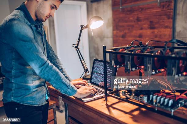 it worker setting up gpus for mining cryptocurrency - cryptocurrency mining stock pictures, royalty-free photos & images