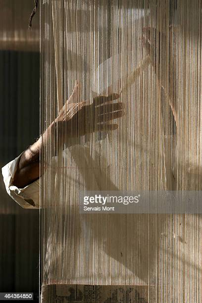 A worker sewing a carpet is seen behind the carpet's strings on October 13 2006 in Hetian Xinjiang province China