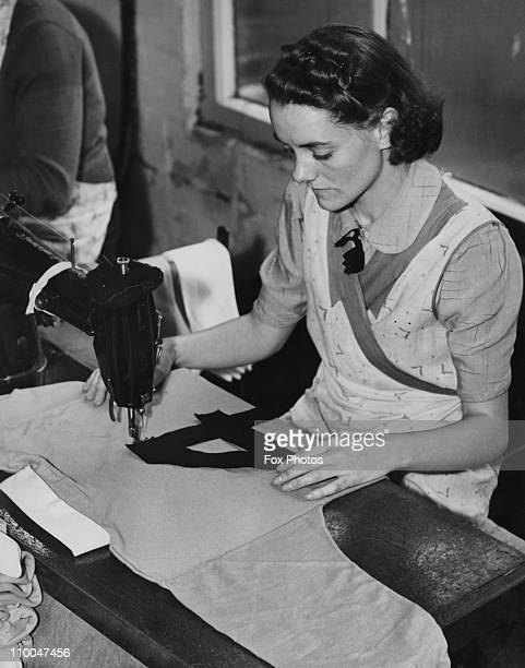 A worker sewing a number onto the back of a Manchester City football shirt at a factory in Wilmslow Cheshire 21st July 1939 Numbered shirts have just...