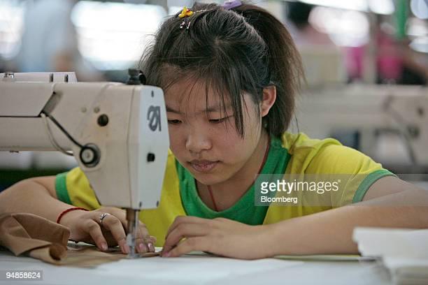 "Worker sews a garment for the ""Venetia"" brand, developed by Jiangsu Sunshine Co. Ltd., at their textile factory at Jiangyin, Jiangsu province, China,..."