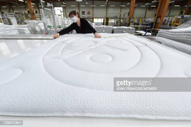 Worker sews the summer-winter mattress trays in the Bultex factory of Noyen-sur-Sarthe, western France, on December 3, 2020. - Created in 1960, the...
