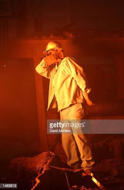A worker shields his face from a blast of heat as he checks on the furnace at the TAMCO steel mini mill on October 4 2002 in Rancho Cucamonga...