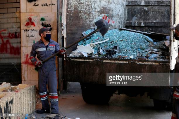 Worker shovels broken glass into the back of a truck while cleaning up after protesters vandalised property overnight during anti-government protests...