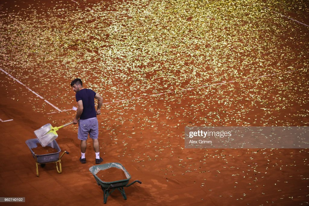 A worker shovels sand and confetti into a pushcart on the centre court after the last match on day 7 of the Porsche Tennis Grand Prix at Porsche-Arena on April 29, 2018 in Stuttgart, Germany.