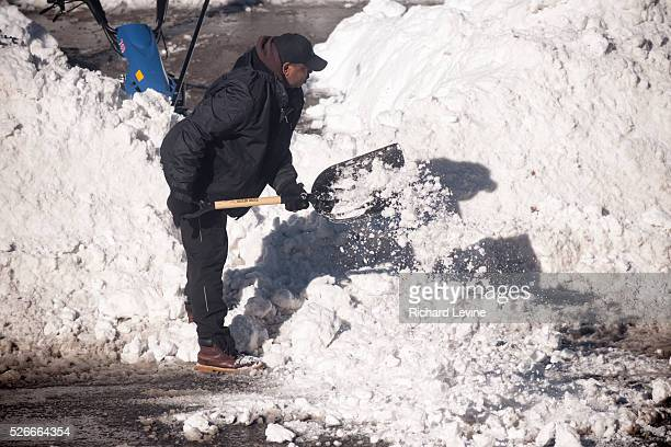 Worker shovels snow in front of a school in the New York neighborhood of Chelsea in the aftermath of Winter Storm Jonas on Sunday, January 24, 2016....