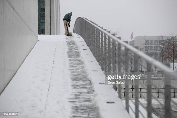 A worker shovels snow near the Reichstag on March 20 2018 in Berlin Germany Snow is falling across Germany and weather forecasts are predicting a...