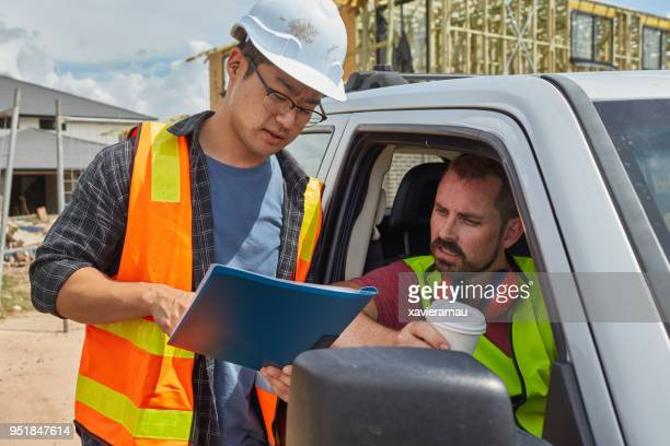 Worker showing file to colleague sitting in car