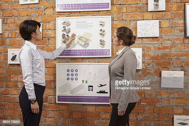 Worker showing framed product to manager on printing and packaging factory wall, China