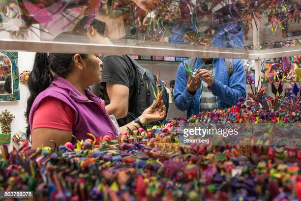 A worker shows alebrijes Mexican folk art sculptures to a customer at the Ciudadela Market in Mexico City Mexico on Tuesday Oct 17 2017 The first...