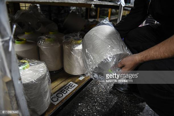 A worker shows copper thread coils in a factory in Santiago on August 14 2016 With the low price of copper Chile develops other uses for the red...