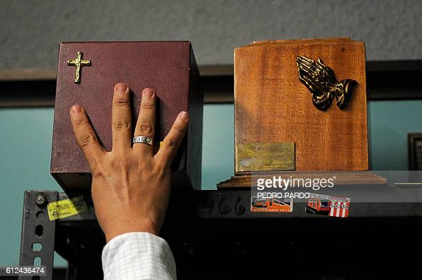 A worker shows funeral urns found in wagons of the metro at the lost property office of the Candelaria transport system station in Mexico City on...