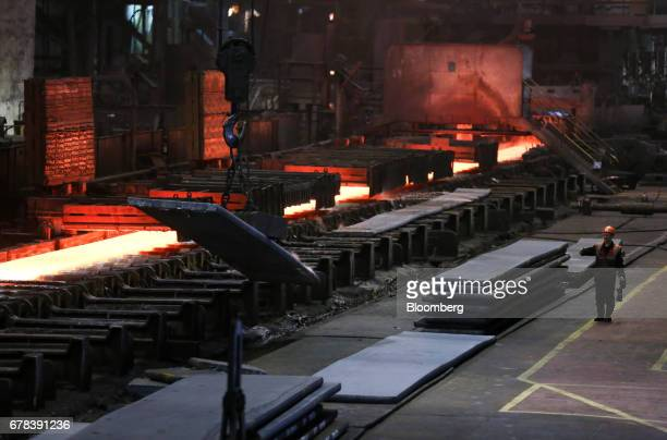 A worker signals to a crane operator as they move cooled iron slabs in the rolling shop at the Cherepovets Steel Mill operated by Severstal PJSC in...