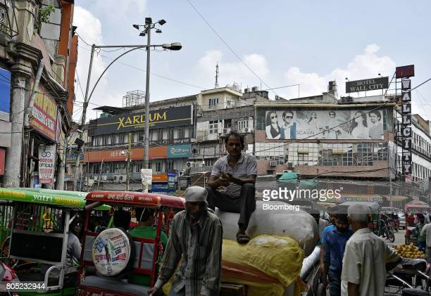 A worker sits at a wholesale market in the Old Delhi area of Delhi India on Saturday July 1 2017 The new goods and services tax was formally ushered...