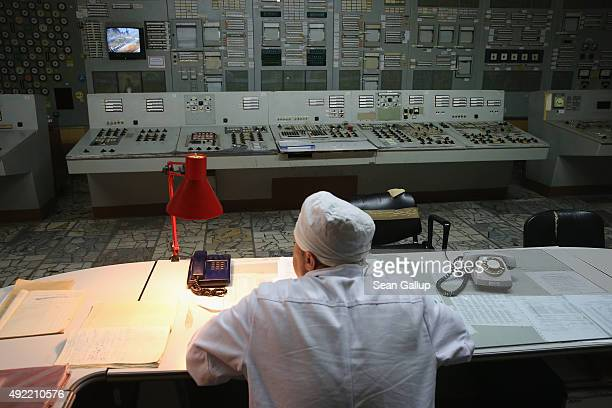 A worker sits at his desk in the control room of reactor number two inside the former Chernobyl nuclear power plant on September 29 2015 near...