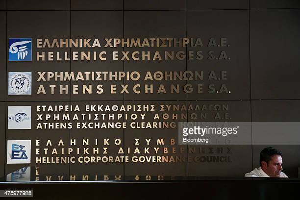 A worker sits behind the reception desk in the Hellenic Stock Exchange in Athens Greece on Friday June 5 2015 The benchmark Athens Stock Exchange...