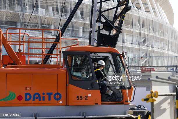 A worker sits in a crane at the construction site of the New National Stadium the main venue for the Tokyo 2020 Olympic and Paralympic Games in Tokyo...