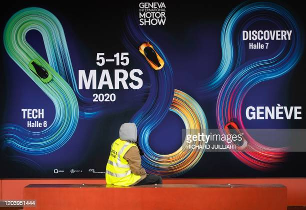 A worker sits next to a banner on February 28 2020 at the Geneva International Motor Show which has been cancelled due to the novel coronavirus...
