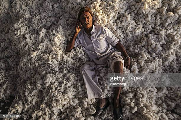 A worker sits on a pile of cotton while talking on a mobile phone at a ginning mill in Wankaner Gujarat India on Wednesday Dec 16 2015 World...