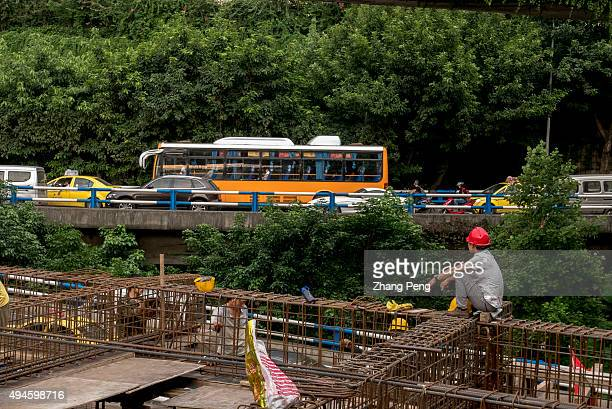 A worker sits on the construction site and looking at the driving car passing by With a growth rate of 11 percent the municipality of Chongqing has...