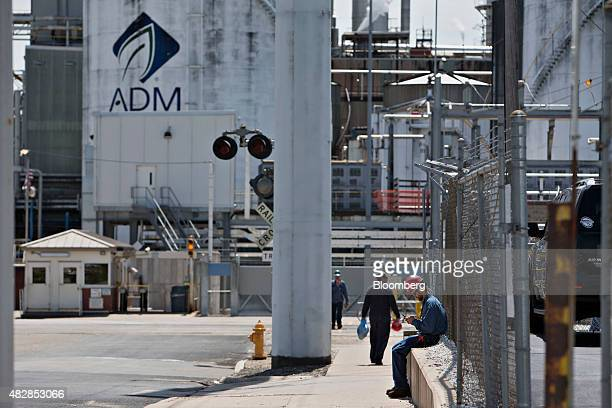 Worker sits outside the Archer Daniels Midland Co. Corn processing plant in Peoria, Illinois, U.S., on Wednesday, July 29, 2015. Archer Daniels...