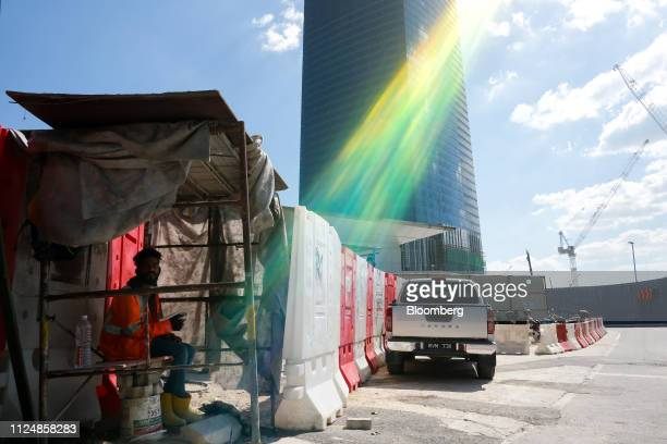 A worker sits under a shelter near the under construction Exchange 106 building on the site of the Exchange TRX precinct in Kuala Lumpur Malaysia on...