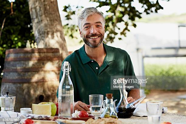 Worker sitting at breakfast table in yard