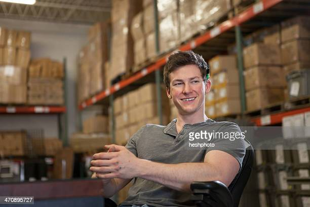 worker sitting in warehouse - heshphoto stock pictures, royalty-free photos & images