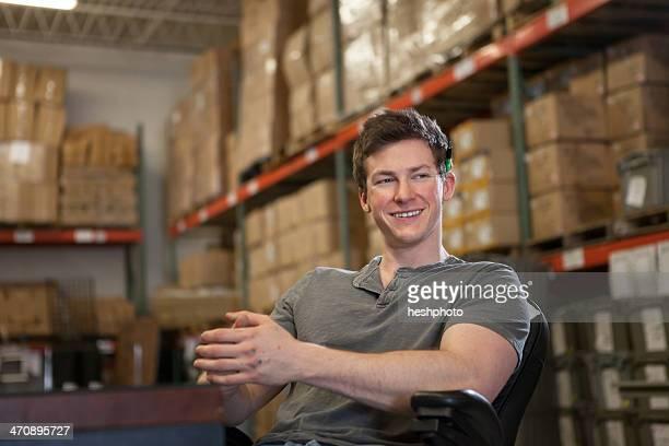 worker sitting in warehouse - heshphoto stock-fotos und bilder