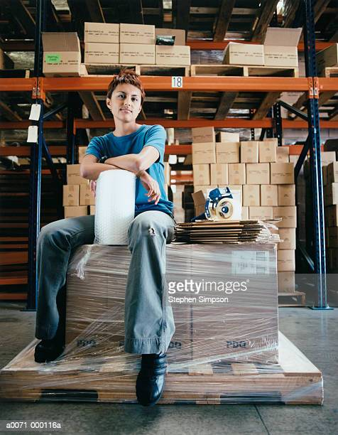 worker sitting on boxes - tape dispenser stock photos and pictures