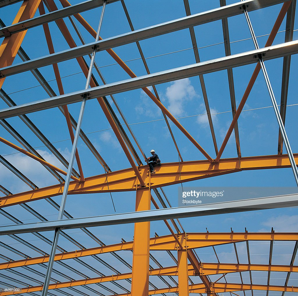 Worker sitting on rafters : Stock Photo