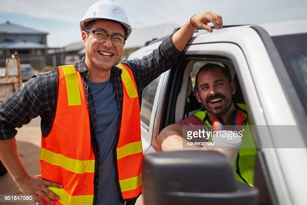 worker smiling by colleague sitting in car at site - occupation stock pictures, royalty-free photos & images