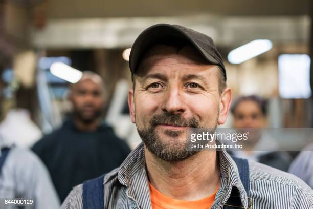 worker smiling in factory - arbeider stockfoto's en -beelden
