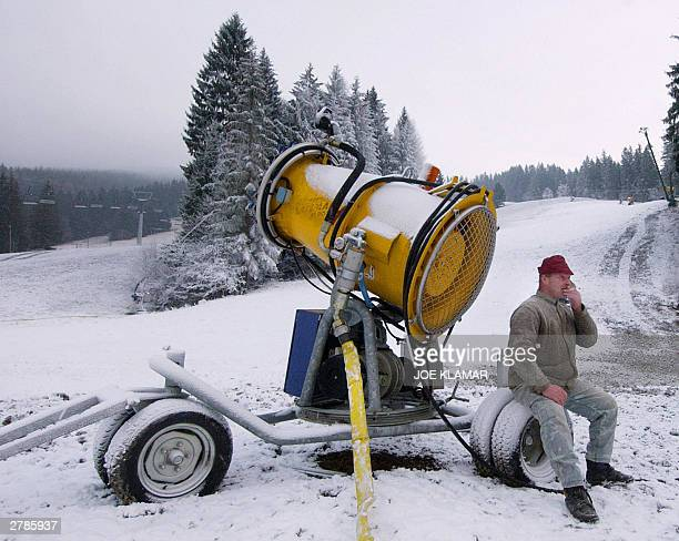 A worker smokes a cigarette as he rests on a snowmaking machine in Slovakia's ski resort of Vratna Dolina 05 December 2003 Vratna Dolina was chosen...