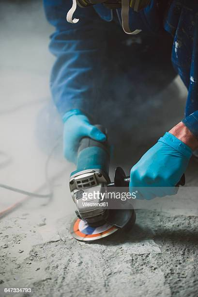 Worker smoothening cement floor with an angle grinder